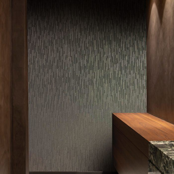 metallic wallcovering with deeply textured vertical stacked blocks which catch the light from every angle in a bathroom interior